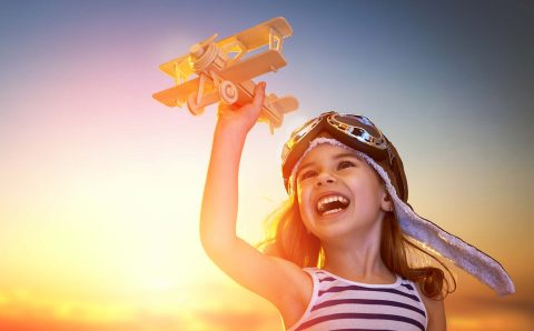 Dreams,Of,Flight!,Child,Playing,With,Toy,Airplane,Against,The